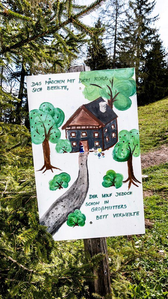 gezeichnete Tafeln am Wegesrand mit einer Märchenszene